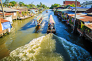 13 JANUARY 2013 - BANGKOK, THAILAND:  Boats navigate Khlong (Canal) Bang Luang in Bangkok. The Bang Luang neighborhood lines Khlong (Canal) Bang Luang in the Thonburi section of Bangkok on the west side of Chao Phraya River. It was established in the late 18th Century by King Taksin the Great after the Burmese sacked the Siamese capital of Ayutthaya. The neighborhood, like most of Thonburi, is relatively undeveloped and still criss crossed by the canals which once made Bangkok famous. It's now a popular day trip from central Bangkok and offers a glimpse into what the city used to be like.    PHOTO BY JACK KURTZ