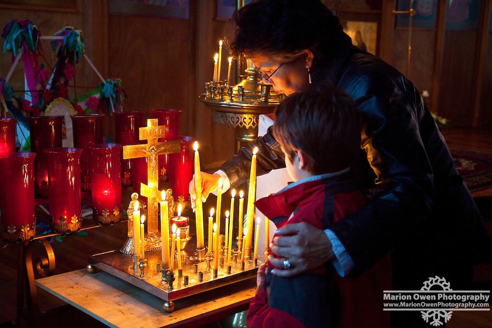 Grandmother helps grandson light candles during Russian Orthodox Christmas service in Kodiak, Alaska