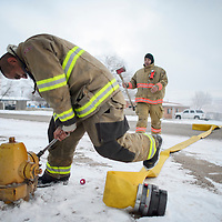 010214       Adron Gardner<br /> <br /> Firefighter Jesse Morris, left, wrenches down on frozen fire hydrant cap ahead of Nalmerthan Pablo while responding to a house fire in Gamerco Friday.