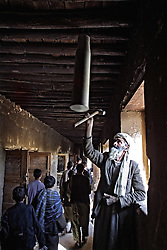 20011013-GULBAHAR, AFGHANISTAN: Afghan elderly man sounds the bell made from shell case to a lesson at a school in Gulbahar, some 30 km from Kabul, 13 October 2001. US warplanes and missiles bombarded Afghan airbases and military camps on Saturday, 13 october 2001, but frustrated opposition forces claimed Washington was not targeting frontline Taliban positions.