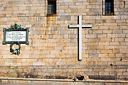 SANTIAGO DE COMPOSTELA, SPAIN - 14th October 2017 - A pilgrim and tourist to Santiago de Compostela relaxes under a cross on the side of a Church nearby to the main square.