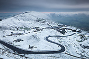 A light snow covering defines the wonderfully winding road that passes between Mam Tor & Rushup Edge before entering into Edale. Rushup Edge can be seen to left side whilst Kinder Scout forms the horizon to the right. Winter landscape photography in Derbyshire's Peak District. January, 2016