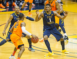 West Virginia Mountaineers forward Jonathan Holton (1) looks to defend Oklahoma State Cowboys guard Anthony Hickey Jr. (12) during the second half at the WVU Coliseum.