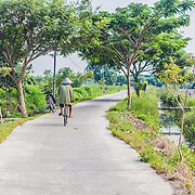 CAPTION: A local fisherman cycles to his fishpond. To the right of the road is a small waterway, which gets clogged up with waste that comes from upstream. LOCATION: Tapak, Semarang, Indonesia. INDIVIDUAL(S) PHOTOGRAPHED: N/A.