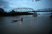 A small boat rides down the Arauca River, which borders Colombia and Venezuela, in the Colombian city of Arauca on June 26, 2009. The border region between Colombia and Venezuela has often been a region with a high level of activity of illegal armed groups. (Photo/Scott Dalton)