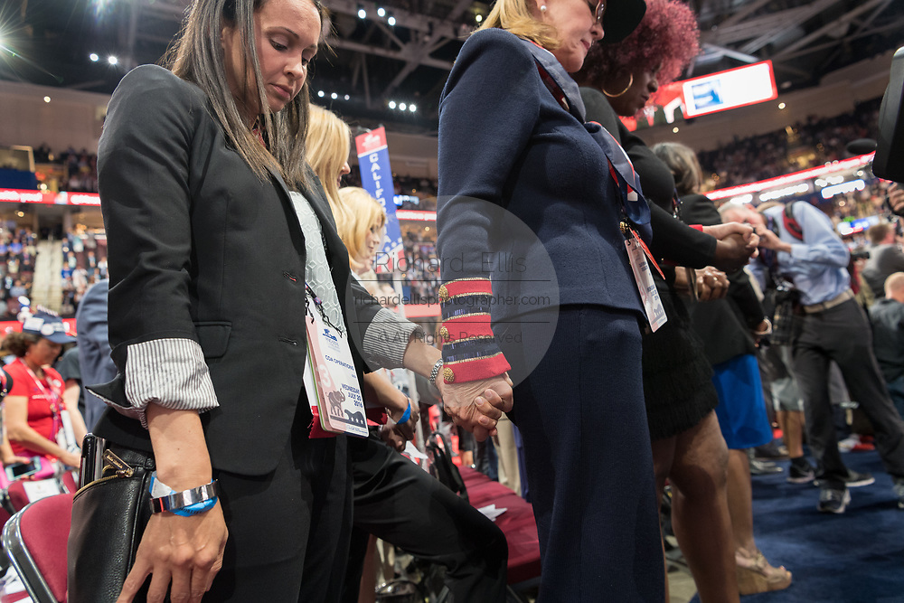 A GOP delegate bow their heads in prayer during the Republican National Convention July 20, 2016 in Cleveland, Ohio.