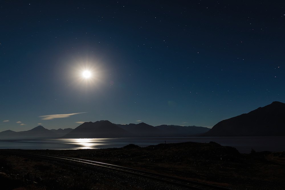 A nearly full moon lights up the waters of Turnagain Arm and the Kenai Mountains in Southcentral Alaska. Autumn. Evening.