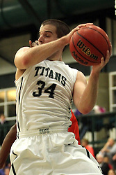 17 November 2015: Ryan Coyle(34) gets the offensive rebound during an NCAA men's division 3 CCIW basketball game between the Greenville College Panthers and the Illinois Wesleyan Titans in Shirk Center, Bloomington IL