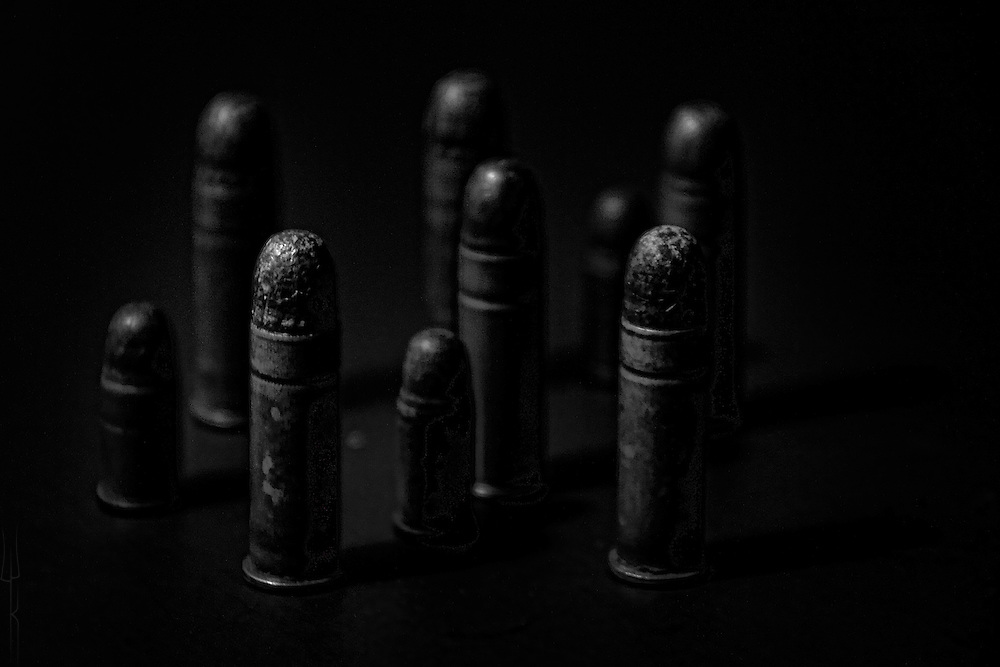 Black and white photograph of nine decaying bullets of different calibers.