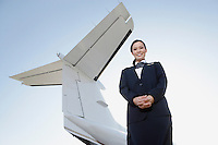 Stewardess in uniform standing below wing of private jet low angle view