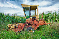 An old rusted harvester abandoned at the edge of a corn field in Connecticut.