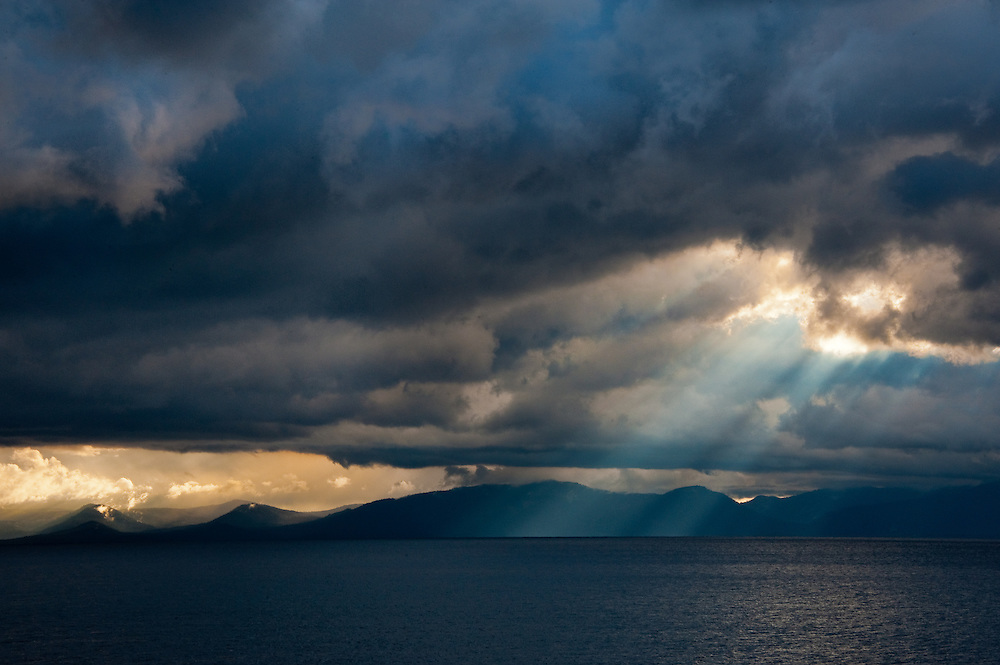 After rain storms pass through Lake Tahoe, dramatic rays of sun shine through the clouds onto the lake and mountains below.