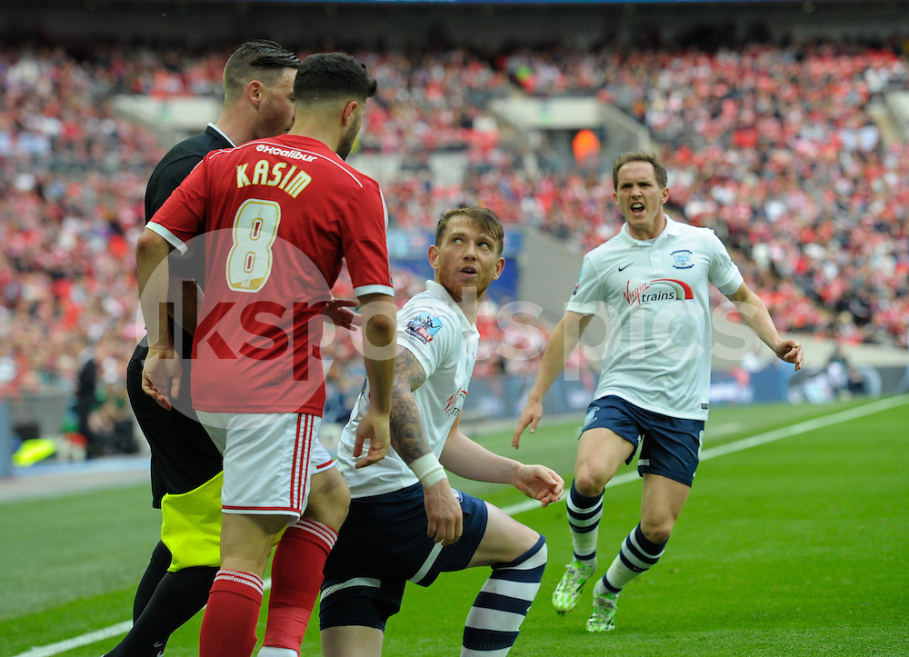 Yaser Kasim of Swindon Town and Joe Garner of Preston North End argue during the Sky Bet League 1 Play-Off Final match between Preston North End and Swindon Town at Wembley Stadium, London, England on 24 May 2015. Photo by Salvio Calabrese.