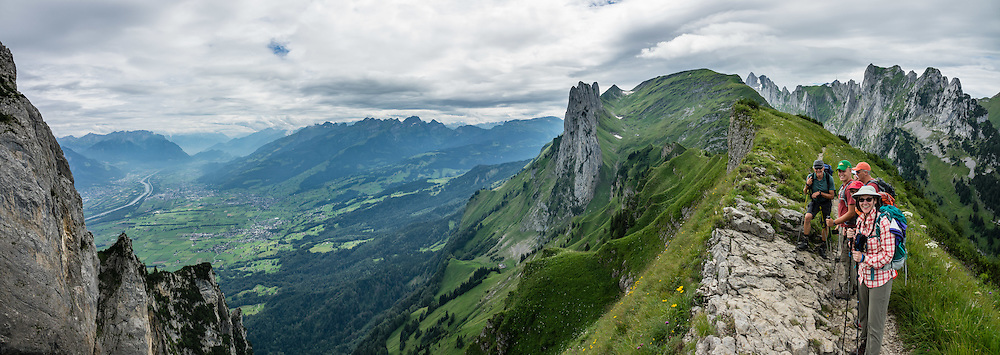 Hauser spire (1951 m, at center) rises above Saxer Lücke pass (1649m) in the Alpstein range, Appenzell Alps, Switzerland, Europe. On left is the Rhine River valley bordering Eastern Switzerland, beyond which is Austria and Lichtenstein. Saxer Lücke is the most prominent geological fault in the Alpstein, forming a fissure or gap in the ridgeline (Lücke=gap). A spectacular ridge walk covered in wildflower gardens starts at Hoher Kasten, reached via cable car from Brülisau, just 10 minutes bus ride from Appenzell village. For a wonderful day hike, take the lift; or staying overnight at Berggasthaus Staubern or beautiful Bollenwees allows time to ascend Hoher Kasten summit (1794 m) on foot. This image was stitched from multiple overlapping photos.