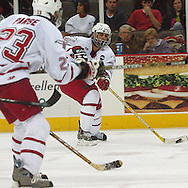 1/07/05 Omaha, Neb.University of  Nebraska at Omaha's No. 25 Bryan Marshall looks to pass the puck to No. 23 Scott Parse Friday night in Qwest Center Omaha. (photo by chris machian/Prarie Pixel Group)