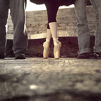 Three people standing at a bus stop, with a ballerina in toe shoes in the middle.