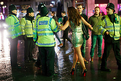 © licensed to London News Pictures. London, UK 01/01/2014. A reveller charing with police officers in Soho, London whilst celebrating the New Year at the first hours of 2014. Photo credit: Tolga Akmen/LNP