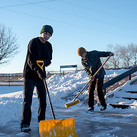 Aaron Morgan, 24, left and RJ Birch, 20, right, start to clear the snow from the new skate park Wednesday evening in Gallup.