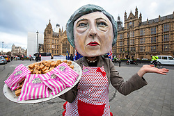 """© Licensed to London News Pictures. 10/12/2018. London, UK. A protester from the campaign group Avaaz wears a Theresa May mask and hands out """"Brexit Fudge"""" as MPs continue to debate the Prime Minister's proposed Brexit deal. Photo credit: Rob Pinney/LNP"""