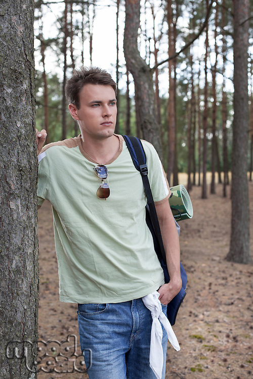 Young man with backpack hiking in woods