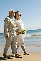 Senior Newlyweds Walking Along Beach
