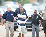 A man (center) has been taken into custody by Oxford Police department training officer Bill Tate (left) and Capt. James Owens following a robbery of the Mississippi Federal Credit Union on West Jackson Avenue in Oxford, Miss. on Wednesday, June 30, 2010.