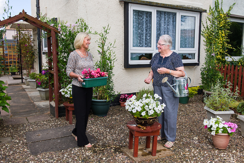 Margaret Ross (Waverley Housing Chief Executive) and Sharon McLean( WH Officer) meeting in the garden of  WH tennant Norma, who is entering th 'Best Kept Garden' comptetion.