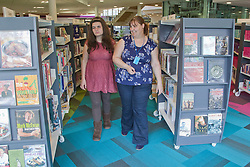 Out reach worker walking through book shelves with visually impaired woman