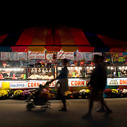 A family walks by an elaborate hot dog stand at night at the 2006 North Carolina State Fair in Raleigh, NC. The family is silhouetted by the stand's artificial lighting.
