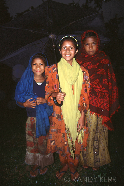 Three nepali girls beneath umbrella