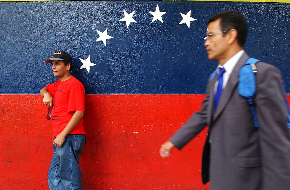 """An unidentified man walks past Orlando Pereira at the """"Esquina Caliente""""(Hot Corner).  Pereira sells pro-government litaerature as well as Chavez and Che Guevara posters.  The corner is a gathering point where supporters of the president come to pass out literature, talk, and pass the time.  It has also been the site of various clashes between police and the Chavistas."""
