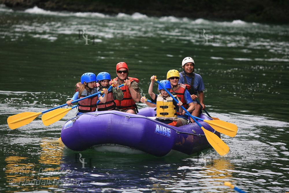 Ecoteach family paddles down Sarapiqui River on whitewater raft trip; Las Horquetas, Costa Rica.