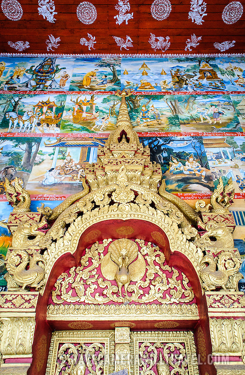 The top of an ornately decorated main door and wall at Wat Phonxay Sanasongkham in Luang Prabang, Laos.