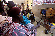 An American documentary about a Los Angeles SWAT police team show being watched by Soumana Natomo and other men and boys in the village of Kouakourou on the banks of the Niger River in Mali. There is no electricity in the village. The television is powered by a car battery that is charged by a photovoltaic solar cell on the roof of the pharmacy behind the men. (Supporting image from the project Hungry Planet: What the World Eats.) The Natomo family is one of the thirty families featured with a weeks worth of food in the book Hungry Planet: What the World Eats.