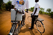 Health workers ride bicycles along a dirt road outside Makango, northern Ghana, as they head to villages to vaccinate children during a national polio immunization exercise on Thursday March 26, 2009.