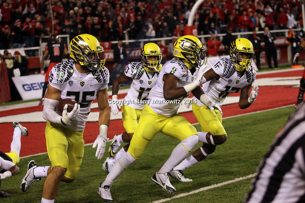 """University of Oregon Ducks' ILB Joe Walker picks up an apparent Utah WR Kaelin Clay TD ball running it back for a 99 yard TD.  Ute's Clay can be seen celebrating his perceived """"TD"""" over Walker's shoulder  at Rice-Eccles Stadium, Salt Lake City, Utah. Photo by Barry Markowitz, 11/8/14, 8pm"""