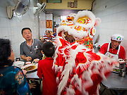 "19 FEBRUARY 2015 - BANGKOK, THAILAND: A lion dance troupe solicits donations in a Chinese restaurant on Chinese New Year in the Chinatown district of Bangkok. 2015 is the Year of Goat in the Chinese zodiac. The Goat is the eighth sign in Chinese astrology and ""8"" is considered to be a lucky number. It symbolizes wisdom, fortune and prosperity. Ethnic Chinese make up nearly 15% of the Thai population. Chinese New Year (also called Tet or Lunar New Year) is widely celebrated in Thailand, especially in urban areas that have large Chinese populations.    PHOTO BY JACK KURTZ"