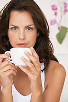 Woman drinking cup of tea half length