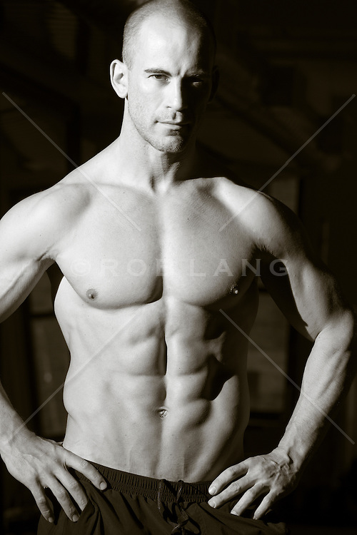 shirtless muscular man with a shaved head