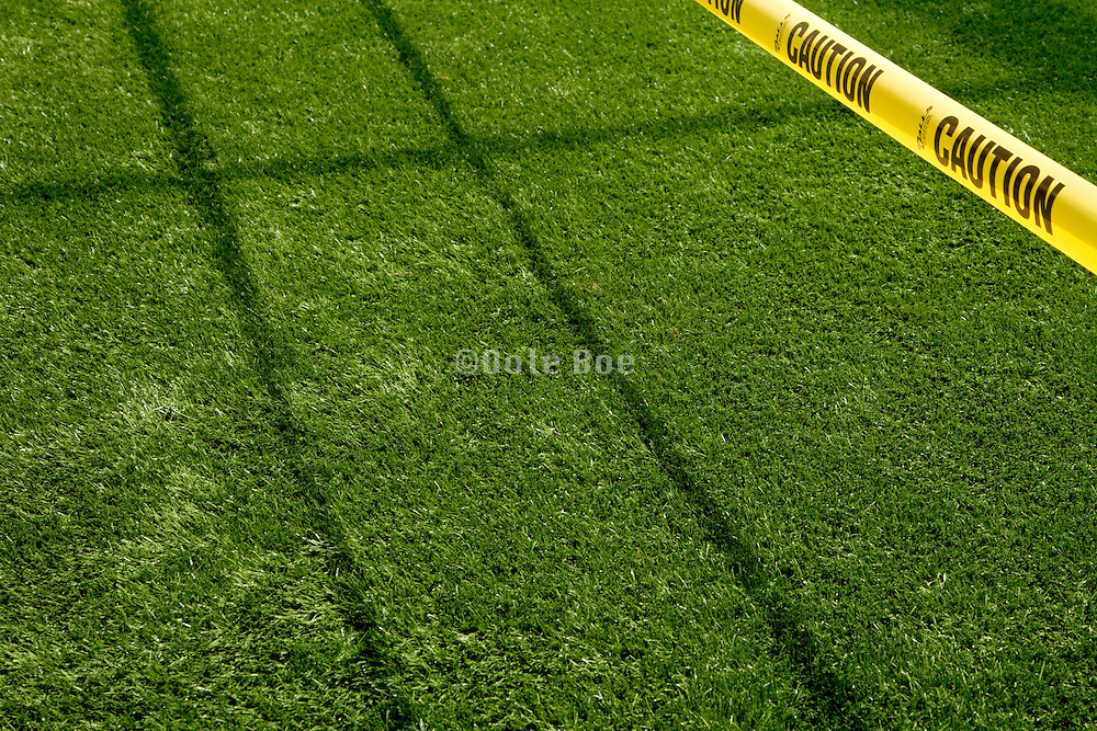 just rolled out  fake plastic grass for golf course with yellow warning caution tape