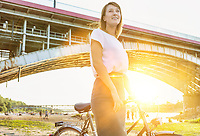Portrait of young attractive businesswoman holding bicycle while walking under the bridge