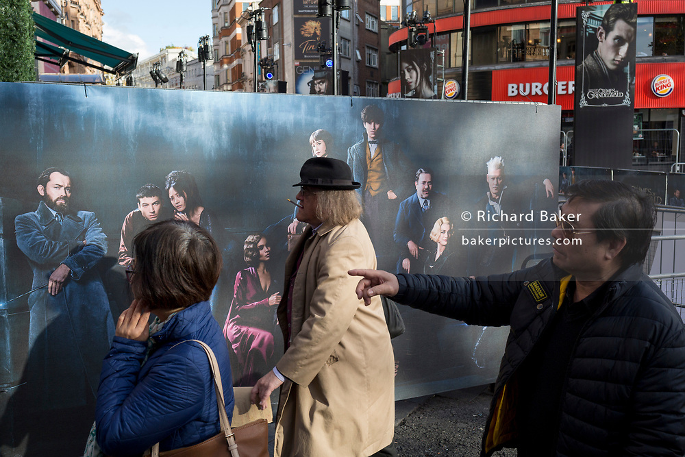Passers-by walk past a publicity banner for the new film 'Fantastic Beasts: The Crimes of Grindelwald', hours before its UK premier in Leicester Square, on 13th November 2018, in London, England.