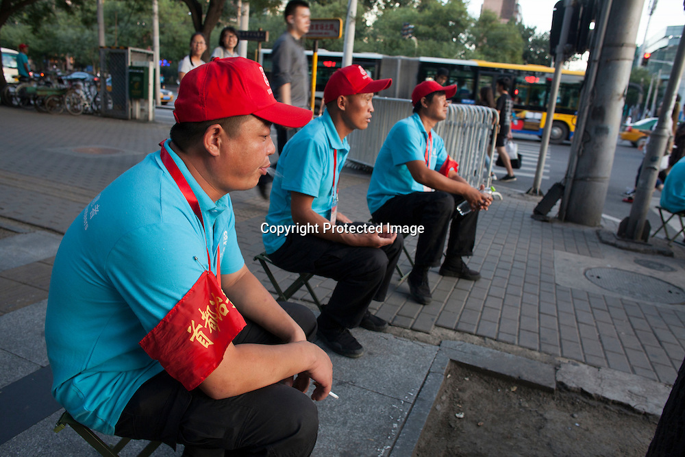 """BEIJING, SEPT.9,2015 : """"volunteers"""" show p in the late afternoon of Sept. 2 to make sure the  sidewalks and streets are gradually emptied for the celebrations to  commemorate the 70th anniversary of the end of World War II."""