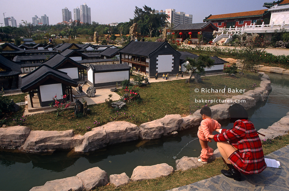 With few visitors to see, a young boy pees into the water surrounding a model town at the Splendid China model village, the 30 hectares large tourist attraction in the city of Shenzhen, China. The kid aims into the water with his mother's help. In the background we see some of the 50,000 ceramic figures and scenes from a period in Chinese history and further away, modern skyscrapers in the metropolis contrasting with ancient, traditional village life. Splendid China is an attraction at the Overseas Chinese Town, Shenzhen that has scaled down replicas of China's historical buildings, wonderful scenes and folk customs. The scale models are of a 1:15 with 100 miniaturized landmarks such as The Terracotta Warriors; Great Wall; Forbidden City; Old Summer Palace etc. all laid out according to their geographic locations.