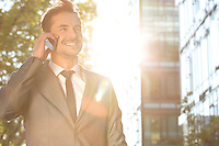 Happy young businessman using cell phone outdoors