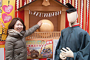 A young Japanese lady touching a good-luck ball in the young people's shopping district of Osu, Nagoya city.