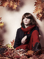 Artistic portrait of a boy sitting on red leaves, childrens fall fashion concept