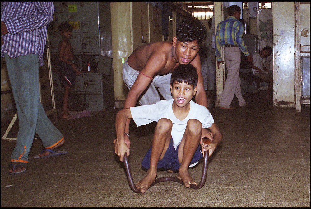 INDIA. Mumbai (Bombay). 2002. Two residents of the shelter have fun by pushing each other around on the floor by sitting on a metal frame of an old chair.