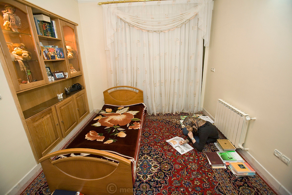 Atefeh Fotowat, a high school student and aspiring fashion designer studies for a University entrance examination seated on a Persian carpet on the floor of her bedroom at her home in Isfahan, Iran. (Atefeh Fotowat is featured in the book What I Eat: Around the World in 80 Diets.)  MODEL RELEASED.