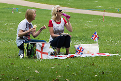 Green Park, London, June 11th 2016. Marking Her Majesty The Queen's official birthday, the Royal King's Horse Artillery fires a 41-Gun-Salute in Green Park. PICTURED: Two patriotic ladies enjoy a picnic in Green Park as they wait for the 41-gun-salute.